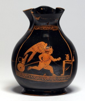 "This small ""chous,"" a vessel for wine, would have been given as a gift to a young boy during the Athenian festival known as the Anthesteria, celebrating the new wine. Such vessels depict children at play, often imitating adults. Here, a chubby Eros runs, pulling a child's toy cart behind him. He wears a wreath, a spiked headdress, and a string of amulets across his chest."